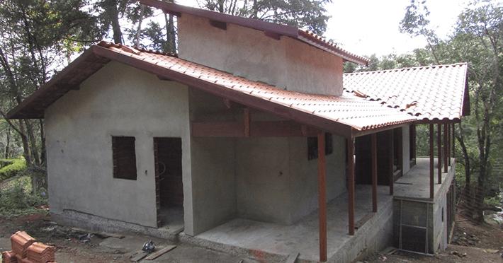 Paredes de madeira e estrutura do telhado finalizadas, instalando telhas.